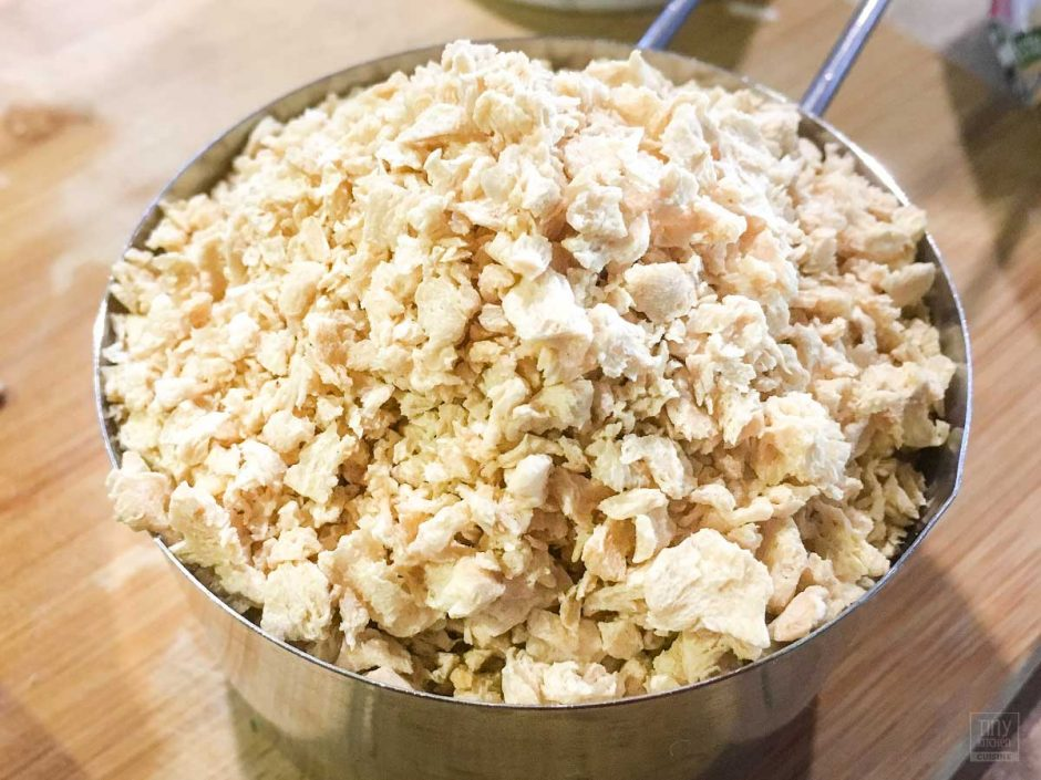 A closeup of textured vegetable protein (TVP) flakes in a metal measuring cup on a wooden cutting board.