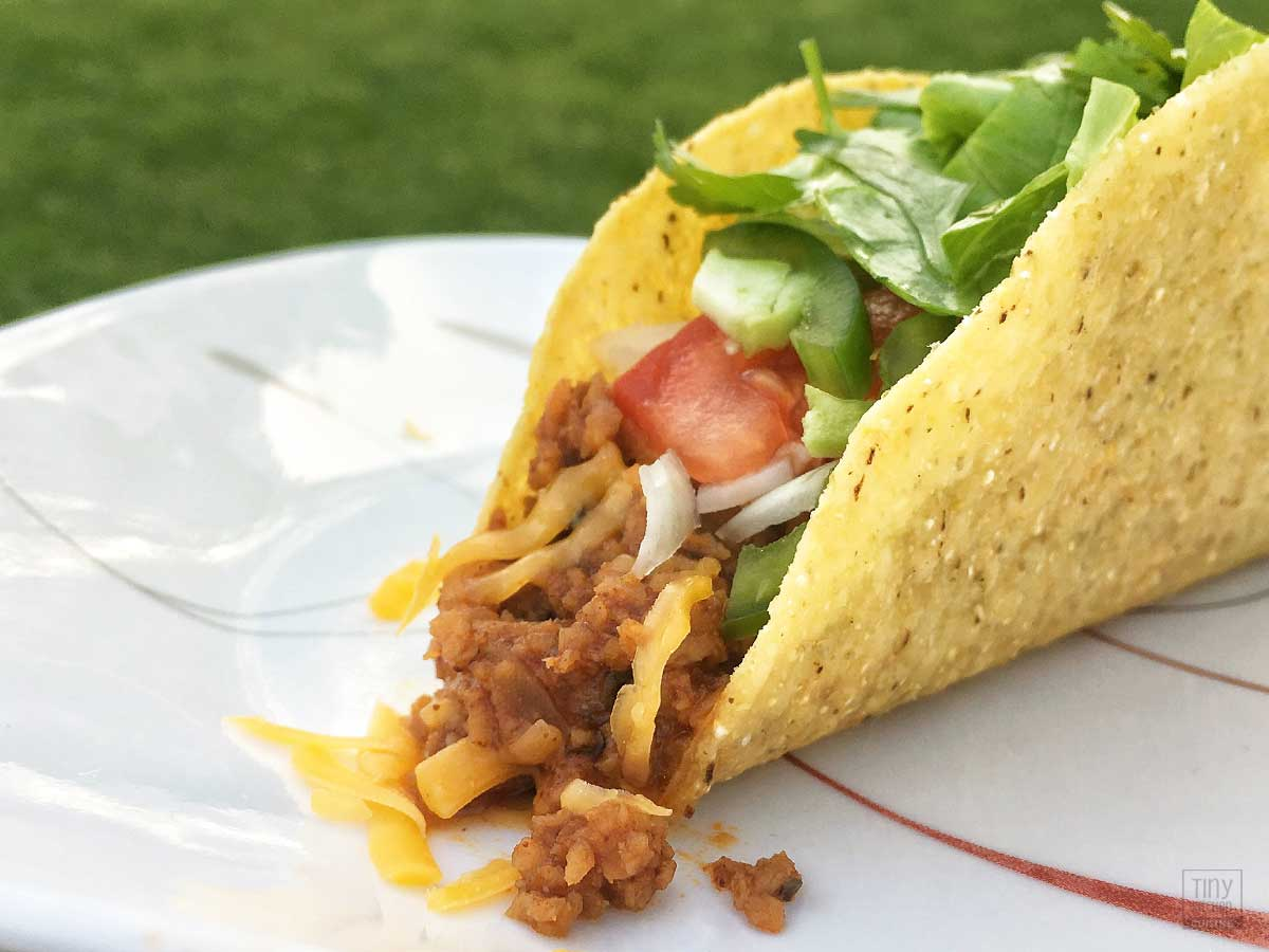 A hardshell TexMex vegetarian taco with lettuce, tomato, and cheese on a plate.