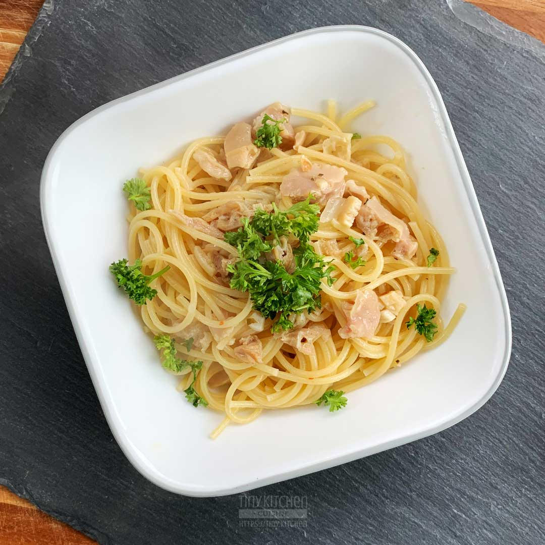 Bowl of spaghetti pasta and clams in a white wine garlic sauce topped with fresh parsley.