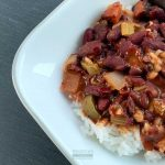 A bowl of stewed red kidney beans and sausage over rice.