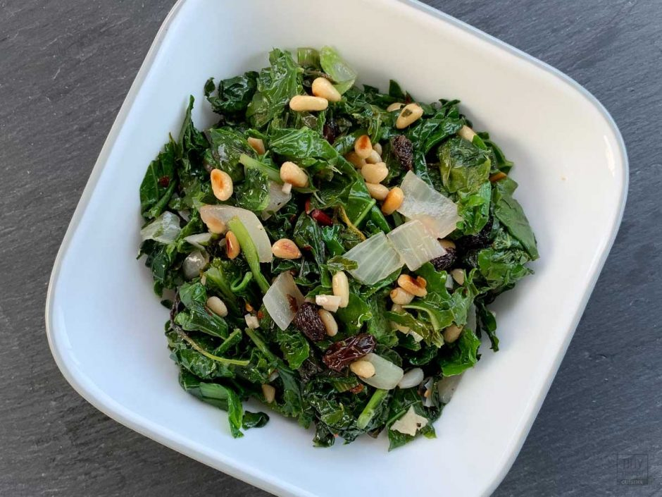 Bowl of mixed braised greens topped with toasted pine nuts and raisins.
