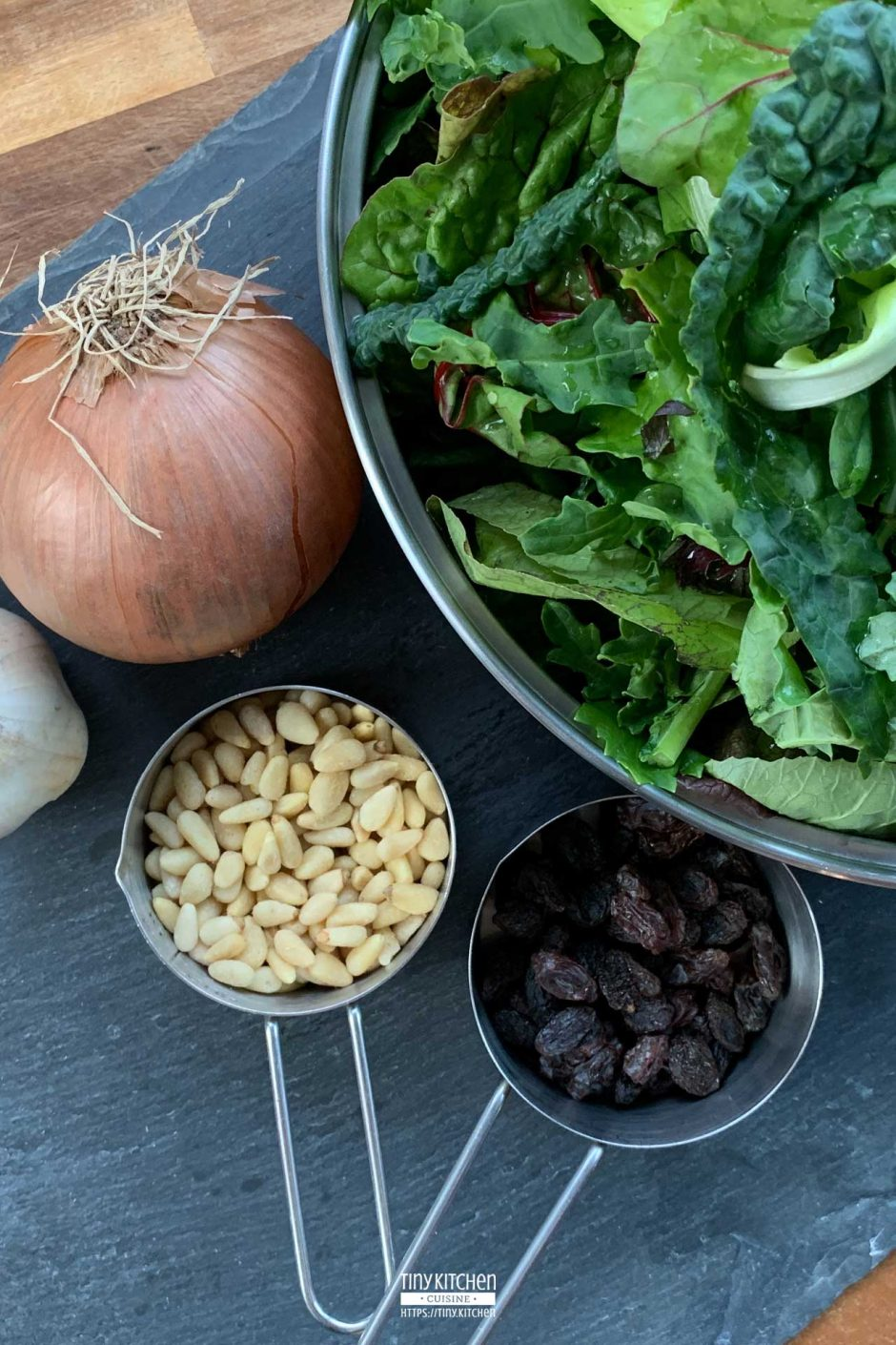 A bowl of fresh mixed braising greens next to an onion, a head of garlic, and two measuring cups filled with pine nuts and raisins.
