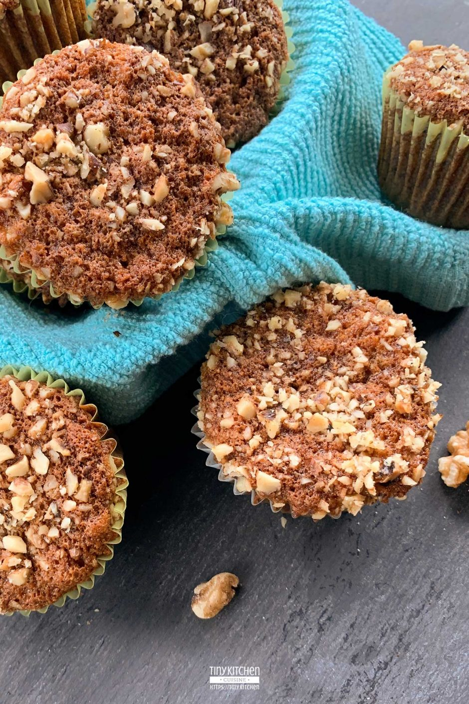 Banana nut muffins piled in a blue cloth lined basket.